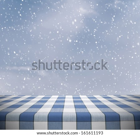 Picnic table template with blue tablecloth on winter sky - stock photo