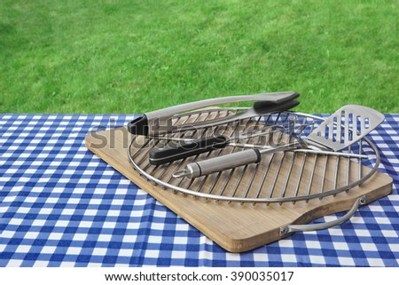 Picnic Table With Checkered Tablecloth, Cutting Board, Grill And Barbecue Tools, Green Lawn In The Background, Summer Outdoor BBQ Party Or Picnic Concept - stock photo