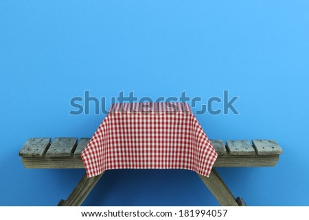 Picnic table with red and white checkered tablecloth and blue background - stock photo