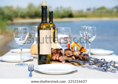 Picnic table with skewers and wine, close-up - stock photo