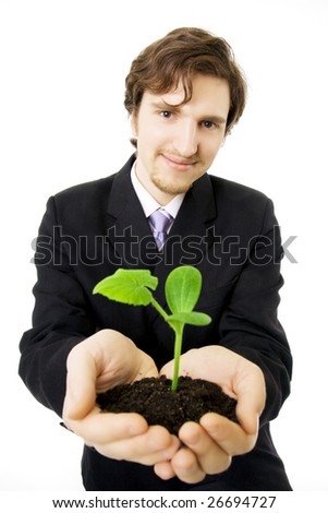 Picture about a businessman who keep in his hands a green sprout - stock photo