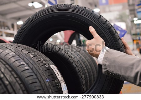 Picture closeup on hands choosing a tire or tyre - stock photo