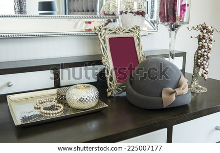 Picture frame and jewelry set on a dresser table in a contemporary room. - stock photo