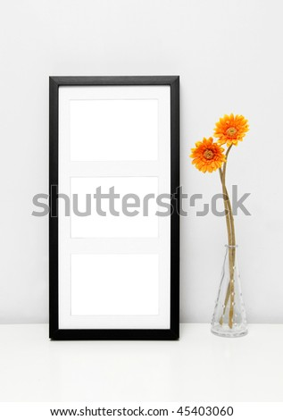 Picture Frame for Home Decoration. Potted sunflowers and a black picture frame on white table against a white wall. - stock photo