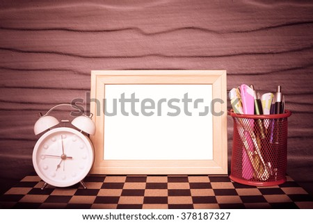 picture frame with clock on chessboard with wooden wall - stock photo