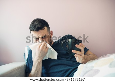 picture from a young man with handkerchief. Sick guy  has runny nose. man makes a cure for the common cold. The patient lies in bed - stock photo