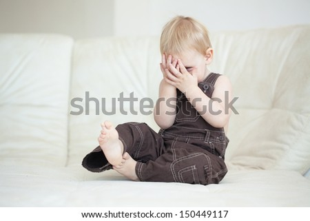 Picture of a baby sitting on a sofa at home - stock photo