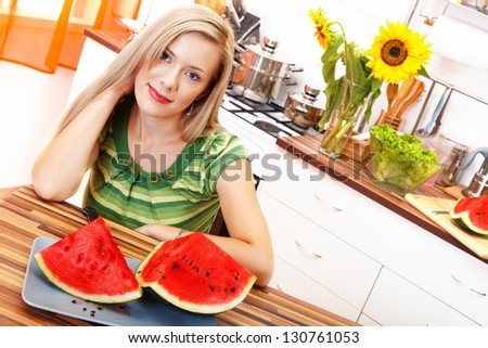 Picture of a beautiful blonde woman with watermelon sitting in the kitchen - stock photo