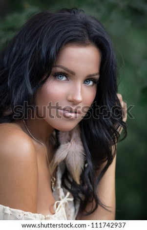 Picture of a beautiful young tanned brunette with fur earring posing outside - stock photo