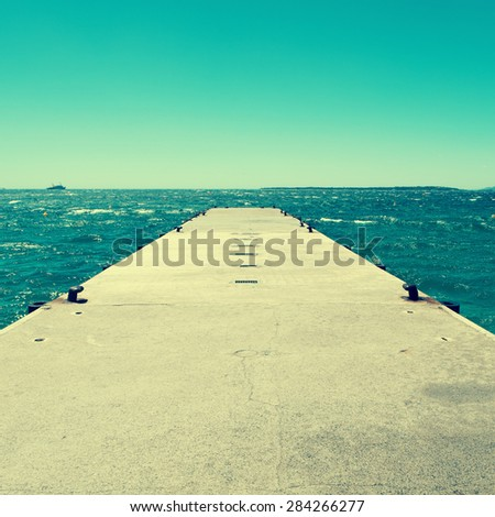 picture of a concrete dock with some mooring bollards in the Mediterranean sea, with a retro effect - stock photo