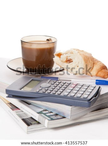 Picture of a cup of coffee, a cornetto and magzines - stock photo