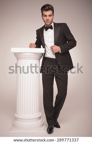 Picture of a elegant business man leaning on a white column while pulling his jacket, full body picture. - stock photo