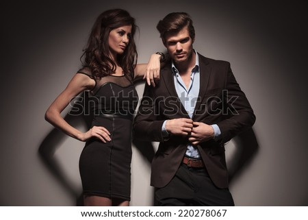 Picture of a elegant fashion couple, the man is unbuttoning his jacket while the woman is looking at him and leaning with one arm. On dark grey background. - stock photo