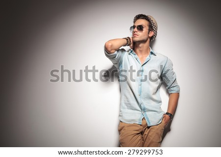 Picture of a fashion man holding his hand to his neck while leaning on a wall, looking up. - stock photo