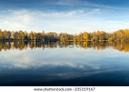 Picture of a lake and trees with colorful leaves on an evening in autumn in Bavaria - stock photo