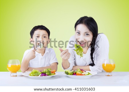Picture of a little Asian boy and his mother eating fresh vegetables salad and drink orange juice - stock photo