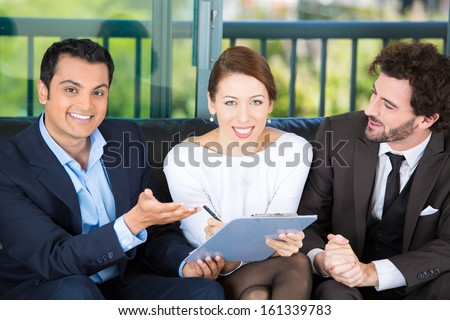 Picture of a manager, financial consultant, banker presenting to a young smiling couple a business investment opportunity plan, offering to sign it, isolated on background of city. Finance decisions - stock photo
