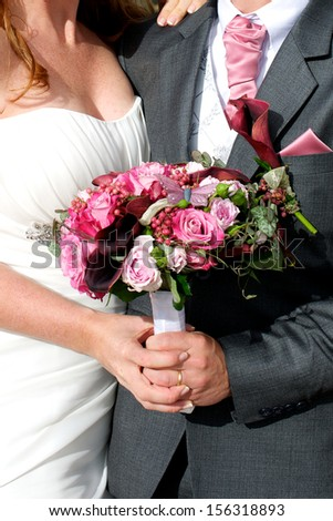 Picture of a newly wed couple holding the wedding bouquet between them - stock photo