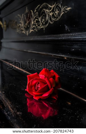 picture of a red rose placed on an old wooden piano that has an antique and vintage design - stock photo