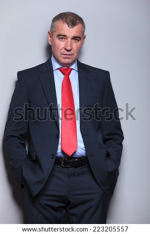 Picture of a serious middle aged business man looking at the camera while holding his hands in pocket, against a grey wall. - stock photo