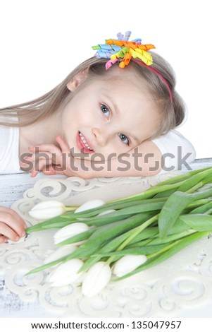 Picture of a smiling little girl with white tulips in hands over white - stock photo