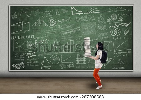 Picture of a student girl carrying a pile of books in classroom - stock photo