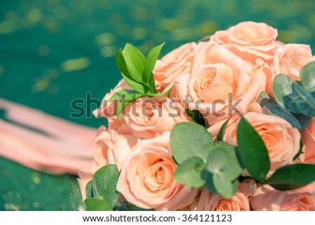 picture of a wedding bouquet , Wedding bouquet of roses lying on green background - stock photo