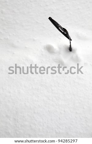 Picture of a windscreen wiper on a windscreen full of snow - stock photo
