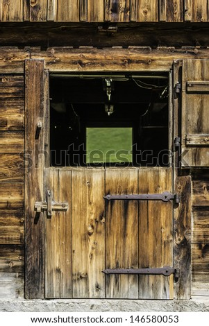 Picture of a wooden door of a stable in the Alps - stock photo