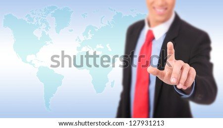 picture of a young businessman pushing an imaginary button against world map - stock photo