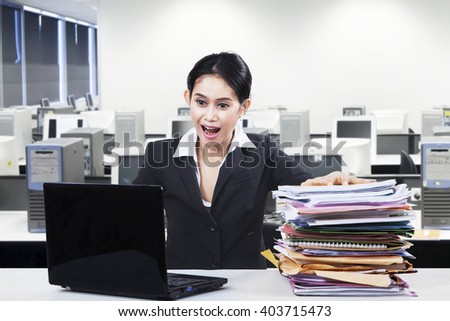 Picture of a young businesswoman looks shocked and happy, looking at laptop computer with a pile of paperwork in the office - stock photo