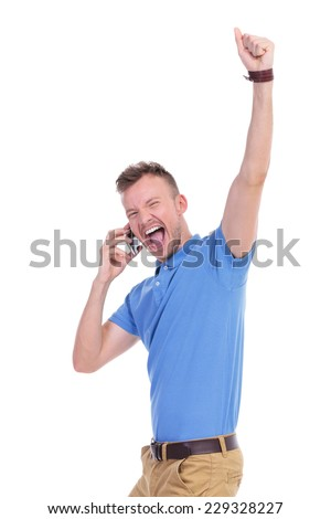 picture of a young casual man cheering on the phone while raising his fist in the air. isolated on a white background - stock photo
