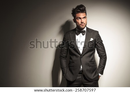 Picture of a young handsome business man looking up while holding both hands in his pocket. - stock photo
