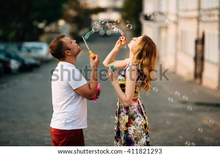 Picture of a young joyful couple blowing bubbles in the city. Close up photo. Pretty man and woman having fun outdoors - stock photo