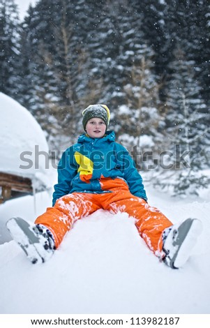 Picture of a young smiling boy sitting in a pile of snow. Trees in the background - stock photo