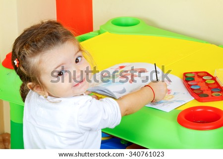 Picture of an adorable little girl in a painting class - stock photo
