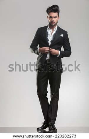 Picture of an elegant young man ajusting his tuxedo while looking at the camera. On grey studio background. - stock photo