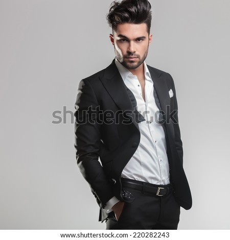Picture of an elegant young man in tuxedo looking at the camera while holding his hands in pocket. On grey background - stock photo