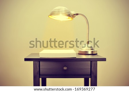 picture of an old gooseneck lamp and a stack of blank paper sheets on a bureau, with a retro effect - stock photo