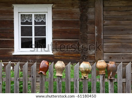 Picture of an old rural house with window and old jugs on the wooden fence - stock photo