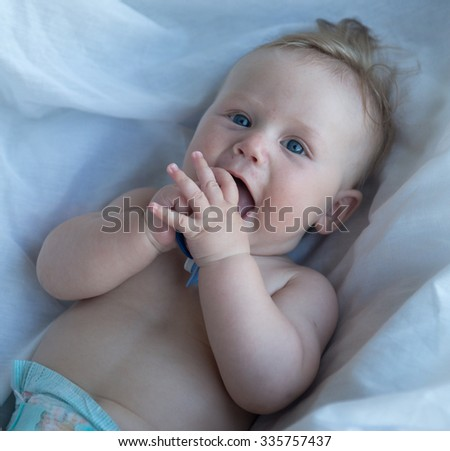 Picture of baby playing with pacifier  in high-key - stock photo