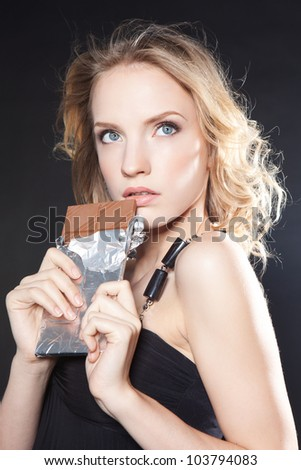 Picture of beautiful blonde fashion girl holding big chocolate bar over black background - stock photo