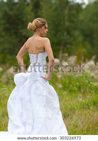 Picture of beautiful bride in white wedding dress in nature - stock photo