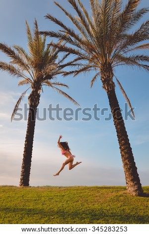 Picture of beautiful excited young woman in pink bikini jumping or dancing beside two palm tree. Pretty girl jumping on summer blue sky tropical background. - stock photo