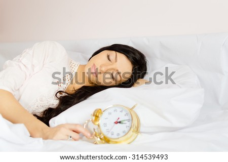 Picture of beautiful girl sleeping in white lace nightclothes. Young woman holding golden retro alarm clock on blurred indoor background. - stock photo