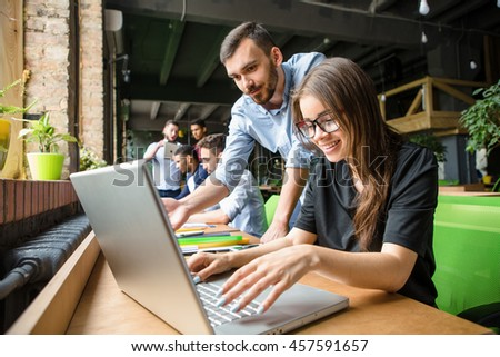 Picture of beautiful lady in glasses listening to her partner or colleague. Businesswoman working on laptop computer in restaurant or cafe. - stock photo