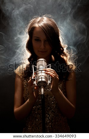Picture of beautiful singer in gold dress with studio microphone - stock photo