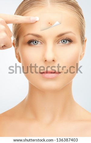 picture of beautiful woman pointing to forehead - stock photo