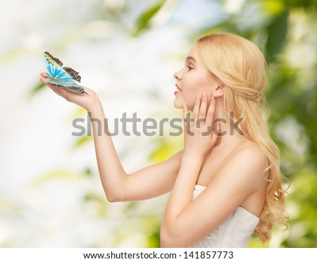 picture of beautiful woman with butterfly in hand - stock photo