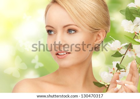 picture of beautiful woman with flowers on twig - stock photo